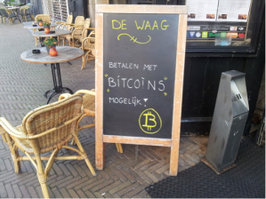 Many vendors are eager to accept bitcoin because it lowers their transaction costs, and it also opens them to a new way of doing business without pulling out your credit card or cash.  It also decreases the worry of storing cash.  Here, a local store in Europe advertises that it accepts bitcoins.  Courtesy of http://www.wikipedia.com