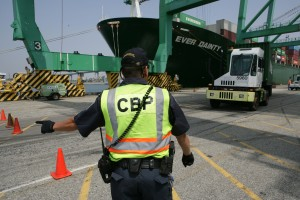 A CBP Officer directs a truck with a seaport container to an inspection area at a port.  www.cbp.gov